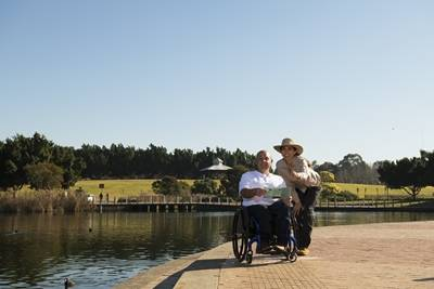 Near lake. Man in wheelchair and lady giving directions
