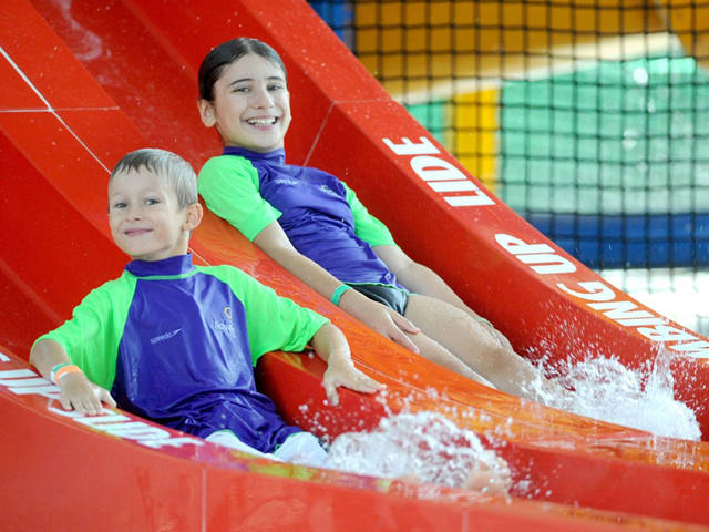 Two boys on water slide at Aquatic Centre all day recreational holiday program
